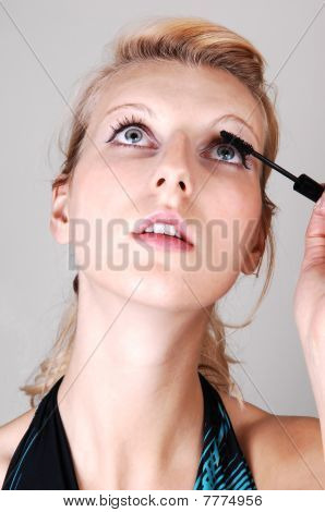 Blond Girl Fixing Her Eyelashes.