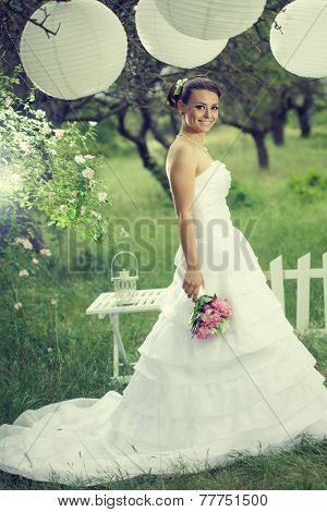 Beautiful bride posing with white decor under paper lanterns in beautiful garden at outdoor wedding ceremony