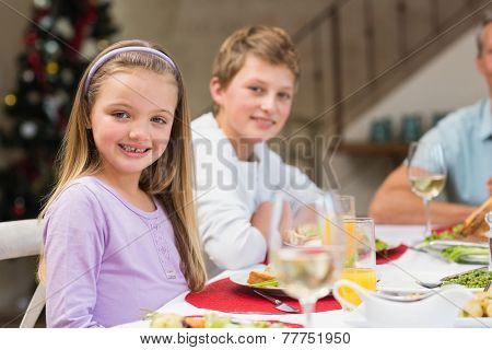 Portrait of smiling little girl at christmas dinner at home in the living room