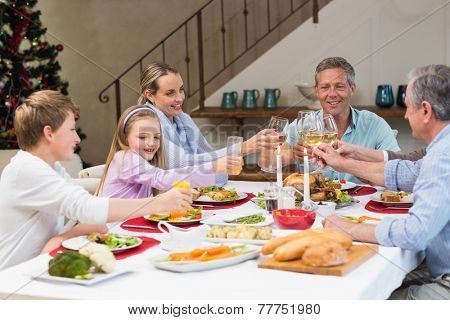 Family toasting with white wine in a christmas dinner at home in the living room