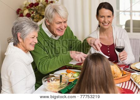 Smiling grandfather carving chicken during christmas dinner at home in the living room