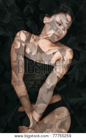Double exposure portrait of atractive woman in lingerie combined with photograph of flowers