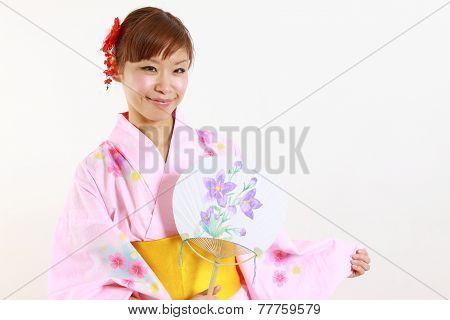 woman wearing Japanese kimono with paper fan