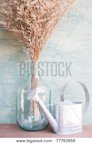 Glass Bottle Of Dried Flower And Watering