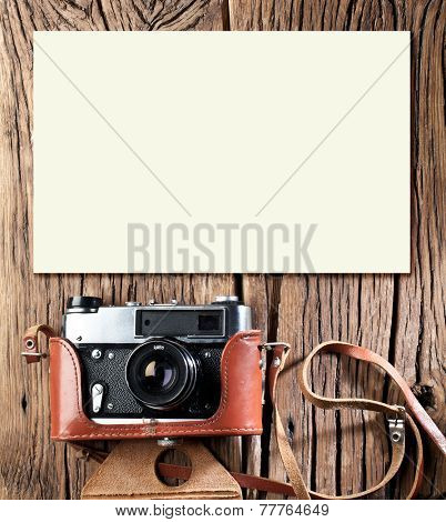 Old rangefinder camera on the old wooden table.