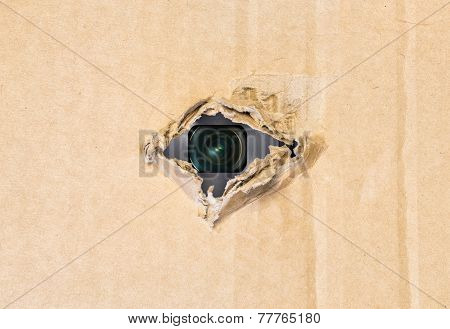 Hidden camera in torn hole in cardboard paper