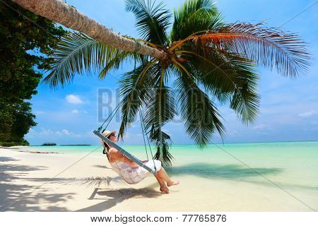 Young beautiful woman relaxing in swing hanging on coconut palm at tropical beach