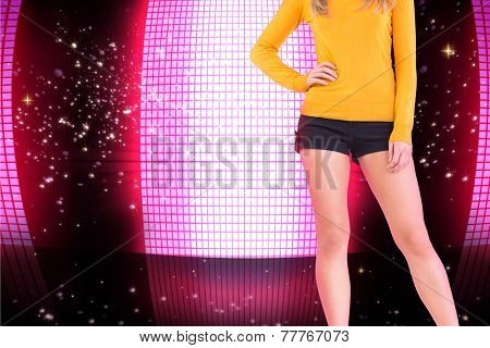 Lower half of woman in boots and shorts against glittering screen on black background