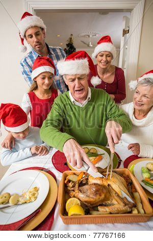 Grandfather in santa hat carving chicken during dinner at home in the living room