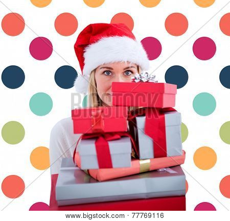 Festive blonde holding pile of gifts against colorful polka dot pattern