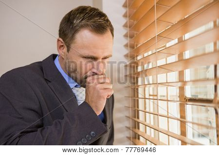Businessman looking out the window and coughing