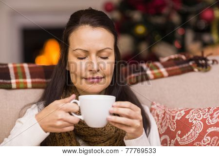 Pretty brunette enjoying hot chocolate at home in the living room