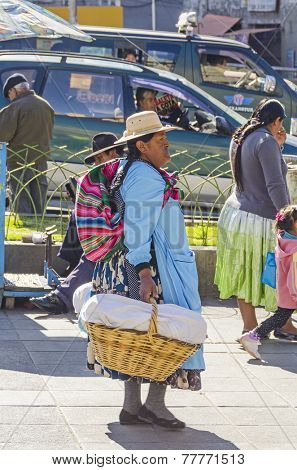 LA PAZ, BOLIVIA, MAY 8, 2014:  Local woman in traditional attire walks with baskets at Plaza San Francisco