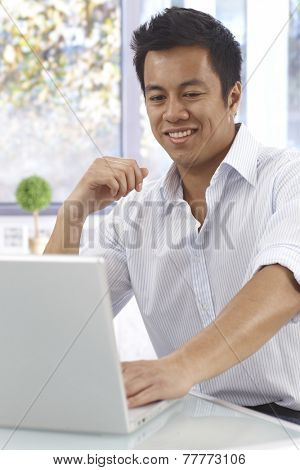 Happy young Asian man using laptop computer, sitting at desk.