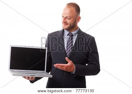 Businessman holding laptop with blank screen, showing laptop with other hand, smiling.