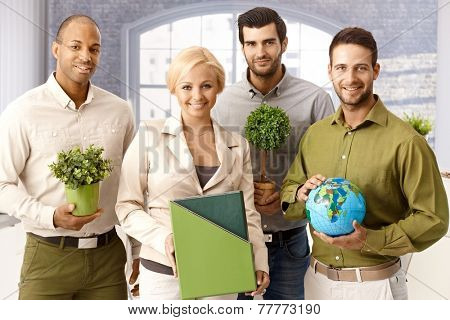 Team portrait of environment friendly businesspeople holding green plants and globe, smiling, looking at camera.