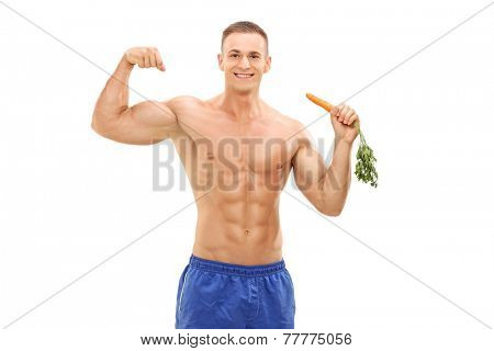 Muscular man holding a carrot and showing bicep isolated on white background