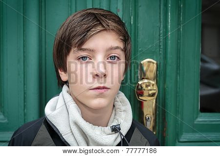 Portrait Of A Beautiful Teenage Boy In Front Of A Green Door
