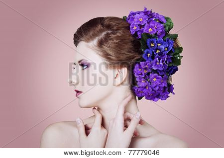 Woman With Viola Flowers In Her Hair On A Turquoise Background