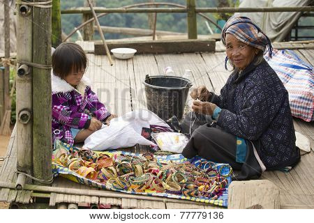 woman and a girl produce traditional hill tribe souvenirs in Doi Ang Khang, Thailand.