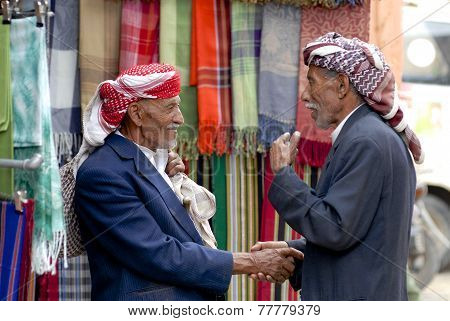 Two unidentified men shake hands at the market in Sana'a, Yemen.
