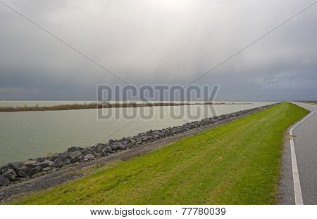 Road on a dike along a lake in autumn