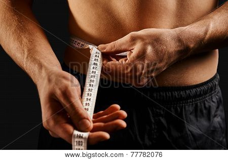Unrecognizable Man Measuring Waist