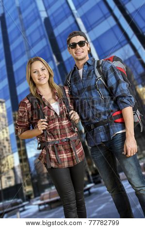Two backpackers, traveling on a shoestring, posing in front of a tall, glass, skyscraper,