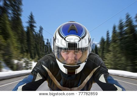Motorcyclist soaring with his bike over a road in beautiful mountain scenics, surrounded by large pine trees and the melting snow in the warm spring sun