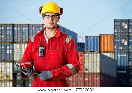 Logistics manager at a container transhipment plant, with an electronic tablet, and cb radio observing safety regulations