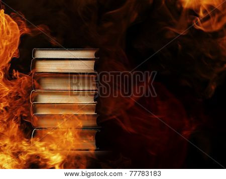 Conceptual image of a tall stack of hardcover books in a burning fire with flames and smoke swirling around them in a darkened room with copyspace