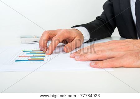 Side View Of Businessman Analysing A Set Of Bar Graphs