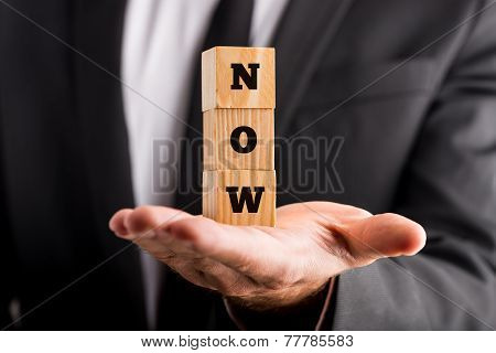 Businessman Holding Wooden Alphabet Blocks Reading - Now