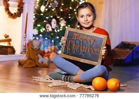 Cute little girl with greeting Merry Christmas