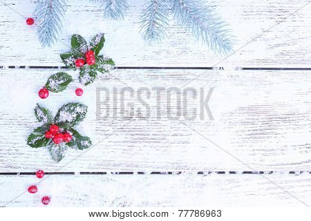 Frame with European Holly (Ilex aquifolium) with berries on wooden background