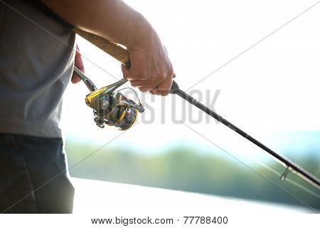 Modern clean fishing rod in hands