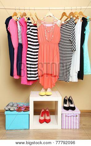 Female dresses on hangers in room