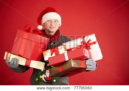 Santa man holding pile of giftboxes