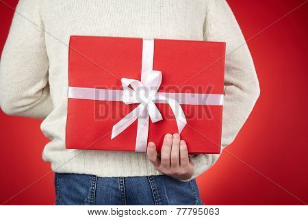 Man in white woolen sweater and jeans hiding red giftbox behind back