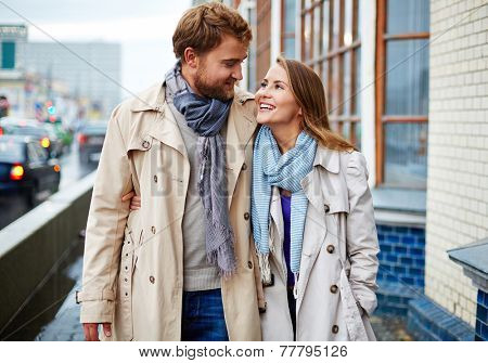 Portrait of affectionate couple in trench coats walking and talking
