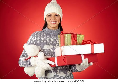 Pretty woman in winterwear holding teddybear and giftboxes