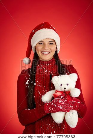 Portrait of happy girl in Santa cap holding fluffy teddybear