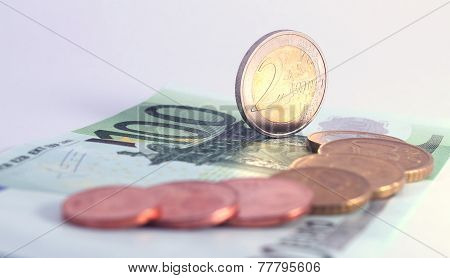 2 Euro Coin Standing Vertically On 100 Euro Note Near Row Of Complete Set Of Euro Coins. Symbol For