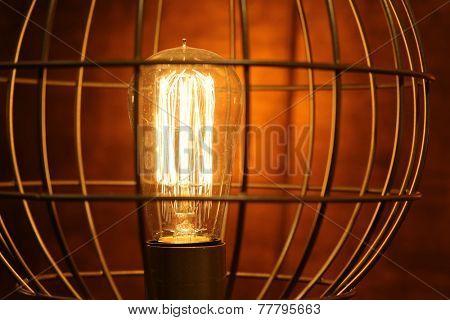 Old dusty light bulb glowing in the dark.
