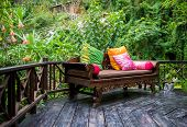 pic of foliage  - Outdoor patio furniture with multicolor pillows on hardwood floor with a lush foliage background - JPG