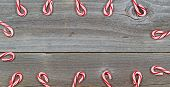 foto of candy cane border  - Top view close up of candy canes forming border on rustic wooden boards - JPG