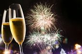 picture of champagne glasses  - Toasting with champagne glasses against fireworks  - JPG