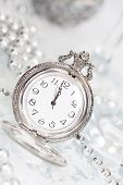 stock photo of midnight  - Old silver clock close to midnight and sparkling Christmas decoration  - JPG