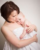 picture of naked children  - Portrait of a beautiful young mother with short brown hair cuddling her baby child both naked wrapped in a white sheet isolated against a light grey - JPG