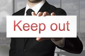 stock photo of underage  - businessman in black suit holding sign keep out - JPG